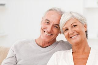 Older couple hugging & smiling l Dental Implants Hermitage PA